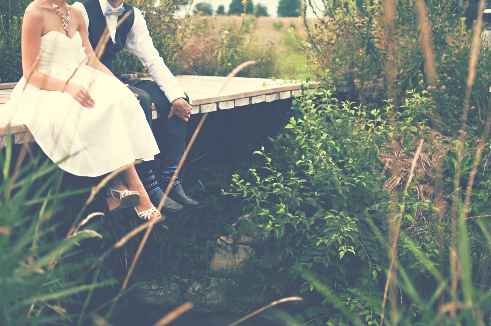 bride-and-groom-sitting-on-wooden-bridge-over-stream